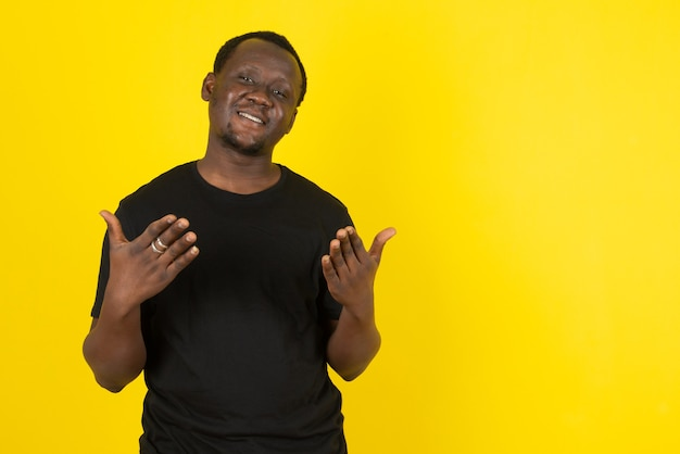 Portret van een jonge man die staat en naar de camera kijkt tegen de gele muur