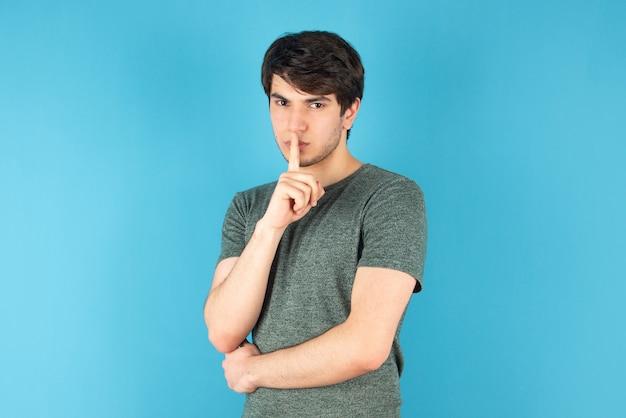 Portret van een jonge man die staat en stil teken doet tegen blauw.