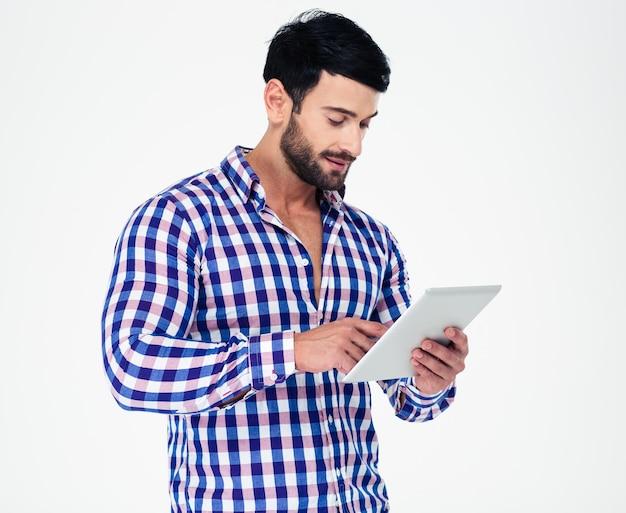 Portret van een jonge man die tabletcomputer met behulp van die op een witte muur wordt geïsoleerd