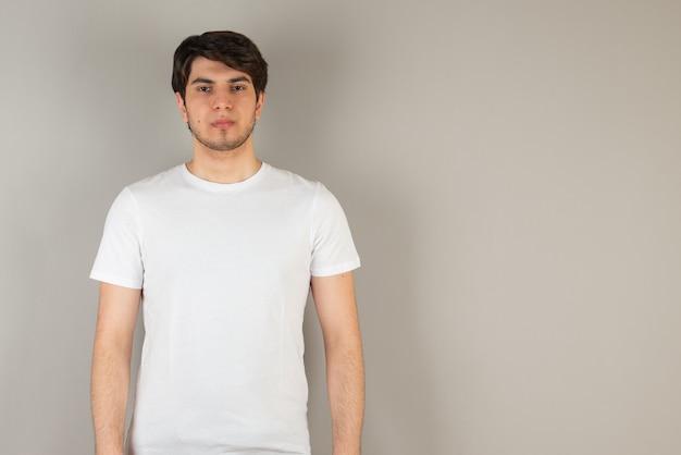 Portret van een jonge man die tegen grijs staat.
