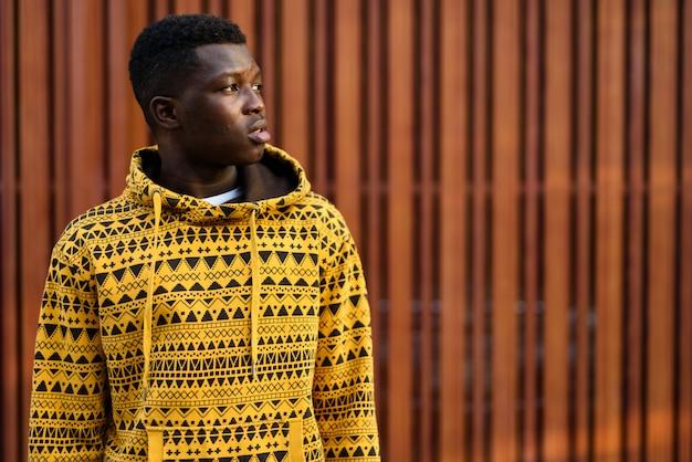 Portret van een jonge man die tegen houten muur denkt