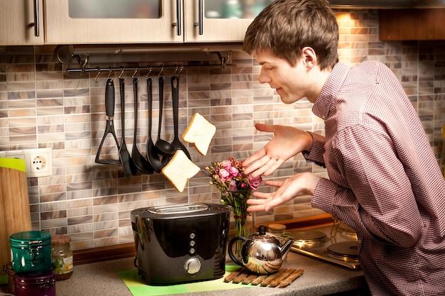 Portret van een jonge man die toast probeert te vangen die uit de broodrooster komt