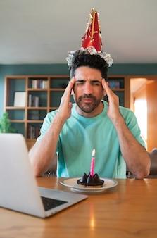 Portret van een jonge man die verjaardag viert tijdens een videogesprek vanuit huis met laptop en een taart.