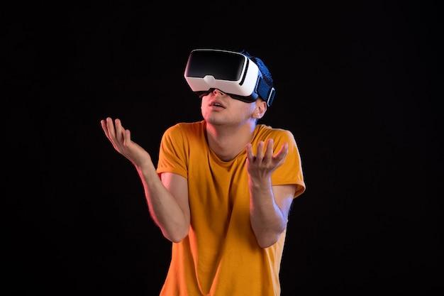 Portret van een jonge man die virtual reality speelt op de donkere muur