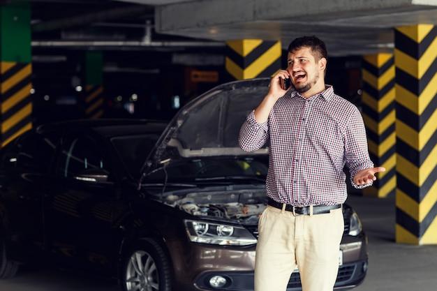 Portret van een jonge man die voor zijn kapotte auto staat en op zijn mobiele telefoon om hulp spreekt