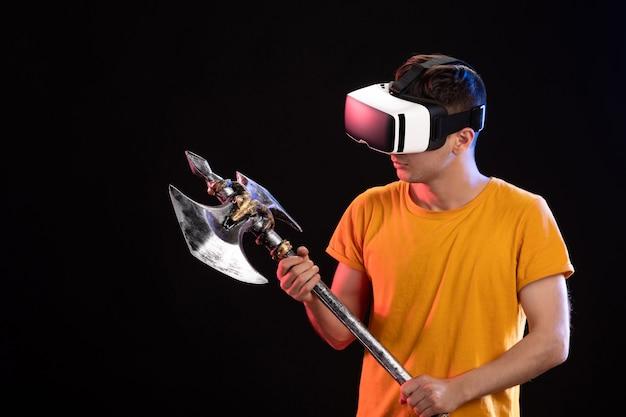 Portret van een jonge man die vr speelt met strijdbijl op donkere muur