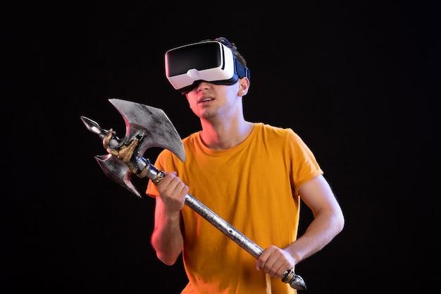 Portret van een jonge man die vr speelt met strijdbijl op donkere vikings samurai d