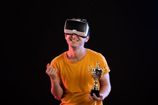 Portret van een jonge man die vr speelt met winnaarbeker op donkere muur