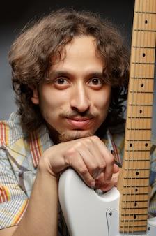 Portret van een jonge man die zich voordeed in de buurt van de elektrische gitaar