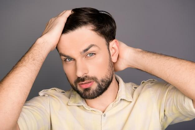 Portret van een jonge man die zijn haar styling