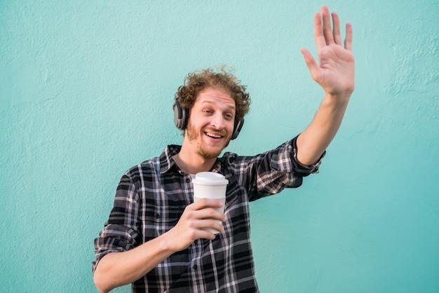 Portret van een jonge man die zijn hand zwaait en glimlach hallo zegt tegen iemand tegen lichtblauwe ruimte.