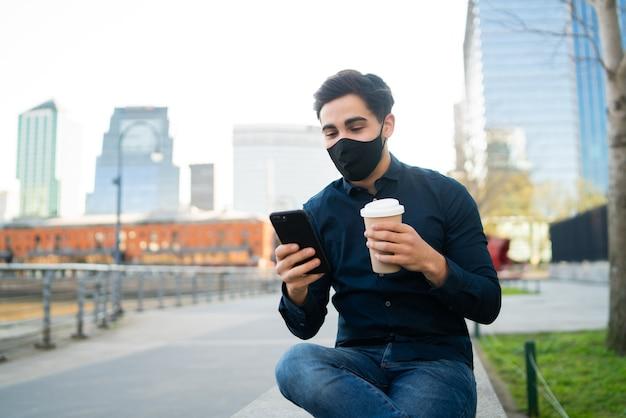 Portret van een jonge man die zijn mobiele telefoon gebruikt en een kopje koffie houdt terwijl hij buiten op de bank zit. nieuw normaal levensstijlconcept. stedelijk concept.