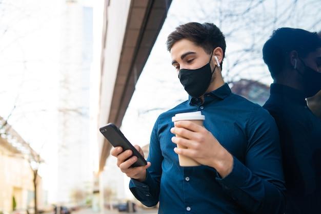 Portret van een jonge man die zijn mobiele telefoon gebruikt en een kopje koffie vasthoudt terwijl hij buiten op straat staat. nieuw normaal levensstijlconcept. stedelijk begrip.