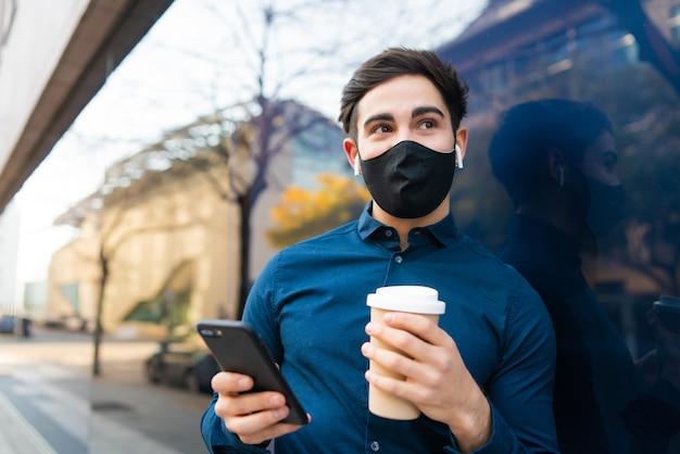 Portret van een jonge man die zijn mobiele telefoon gebruikt en een kopje koffie vasthoudt terwijl hij buiten op straat staat. nieuw normaal levensstijlconcept. stedelijk concept.