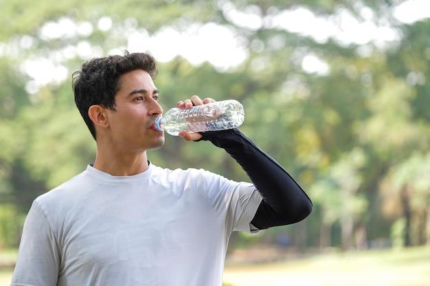 Portret van een jonge man drinkwater in park na het hardlopen in de ochtend