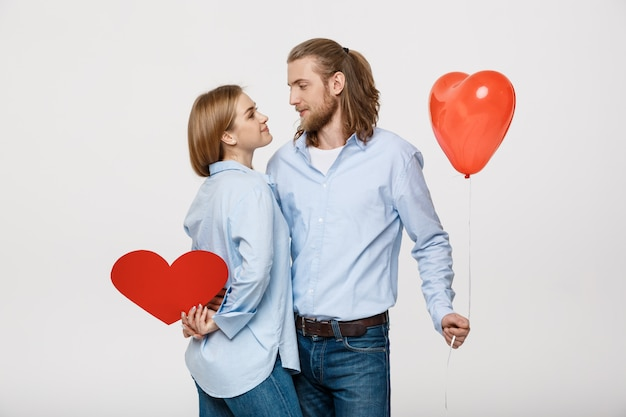Portret van een jonge man en vrouw met een hartvormige ballon en papier