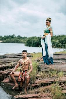 Portret van een jonge man en vrouw met een prachtig traditioneel kostuum poseren in de natuur in thailand
