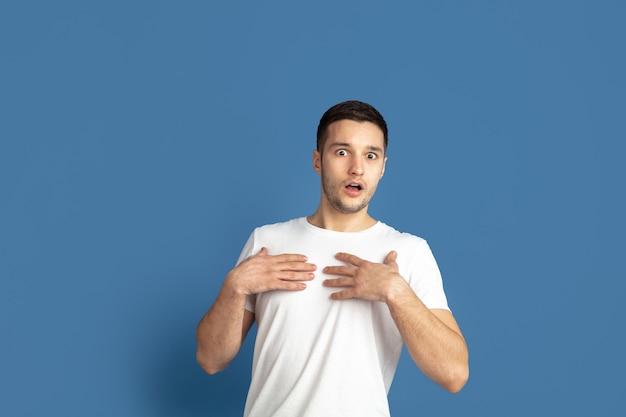 Portret van een jonge man geïsoleerd op blauwe studio wall