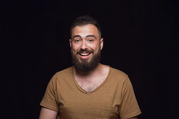 Portret van een jonge man geïsoleerd op zwarte muur close-up. photoshot van echte emoties van mannelijk model. benieuwd, spannend en verbaasd. gelaatsuitdrukking, concept van menselijke emoties.