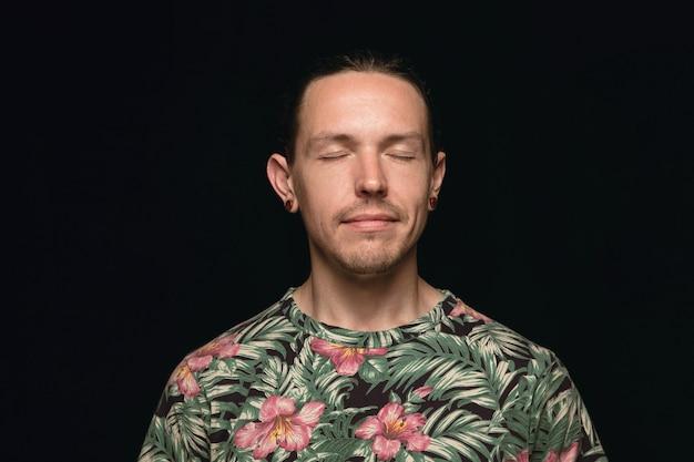 Portret van een jonge man geïsoleerd op zwarte ruimte close-up. denken en glimlachen