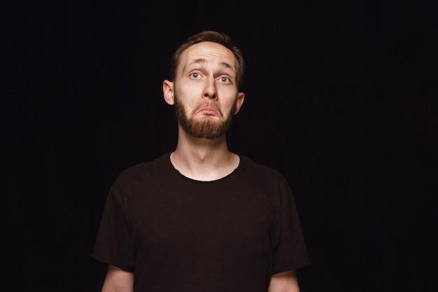 Portret van een jonge man geïsoleerd op zwarte studio achtergrond close-up. benieuwd, opwindend en verbaasd.