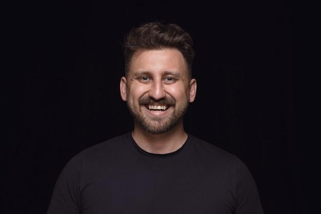 Portret van een jonge man geïsoleerd op zwarte studio achtergrond close-up. photoshot van echte emoties van mannelijk model. glimlachen, zich gek gelukkig voelen, lachen. gelaatsuitdrukking, concept van menselijke emoties.