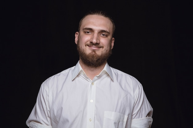 Portret van een jonge man geïsoleerd op zwarte studio achtergrond close-up. photoshot van echte emoties van mannelijk model. glimlachen, zich gelukkig voelen. gelaatsuitdrukking, puur en duidelijk concept van menselijke emoties.