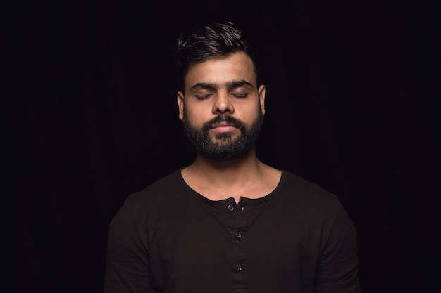 Portret van een jonge man geïsoleerd op zwarte studio achtergrond close-up. photoshot van echte emoties van mannelijk model met gesloten ogen. attent. gelaatsuitdrukking, menselijke aard en emoties concept.