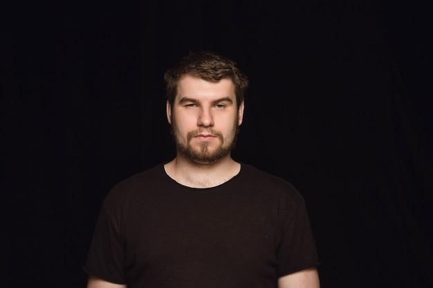 Portret van een jonge man geïsoleerd op zwarte studio close-up