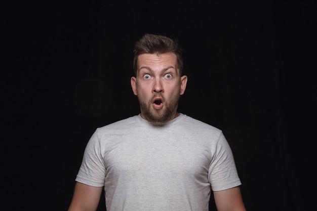 Portret van een jonge man geïsoleerd op zwarte studio muur close-up. echte emoties van mannelijk model. benieuwd, spannend en verbaasd. gelaatsuitdrukking, concept van menselijke emoties.
