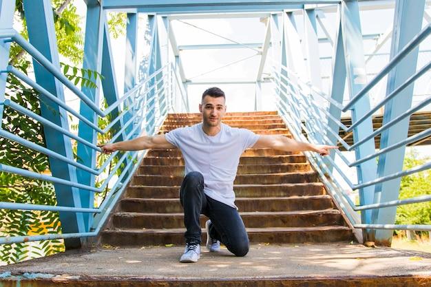 Portret van een jonge man geknield op trappen zijn armen strekken
