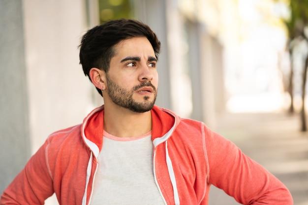 Portret van een jonge man gestrest en bezorgd over iets terwijl hij buiten stond