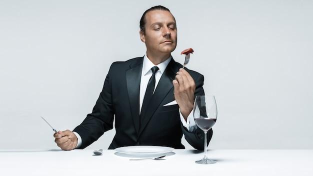Portret van een jonge man in beeld van maniak met mes, vork en en een stuk rauw vlees op een bord. man in pak. het beeld in de stijl van halloween