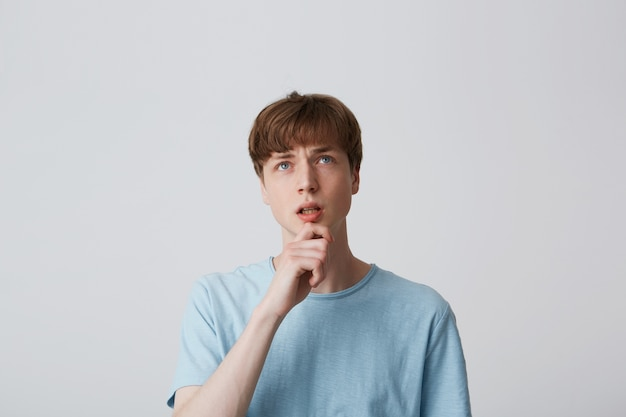 Portret van een jonge man in blauw t-shirt, houdt de arm op de kin en wordt opgezocht
