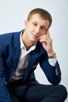 Portret van een jonge man in een blauwe jas op een witte muur