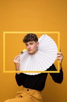 Portret van een jonge man in een gele scène achter een frame