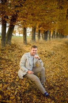 Portret van een jonge man in een jas. een man zit op de grond.