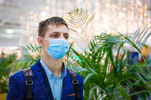Portret van een jonge man in een jas en een medisch masker in een winkelcentrum