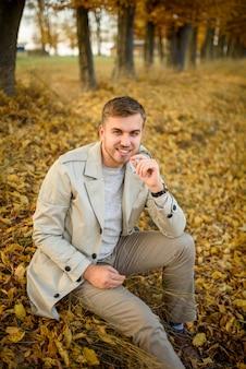 Portret van een jonge man in een jas op herfst bomen. een man zit op de grond.