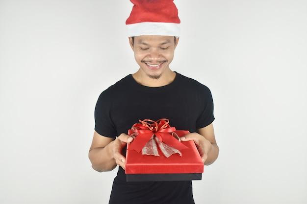 Portret van een jonge man in een kerstmuts die lacht met een rode geschenkdoos op een grijze achtergrond