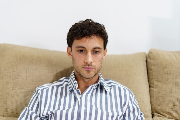 Portret van een jonge man in een overhemd met een geconcentreerde uitdrukking op een bank