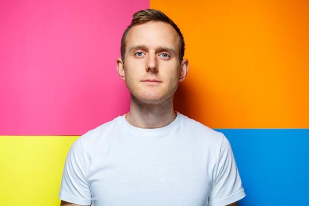 Portret van een jonge man in een wit t-shirt die naar de camera kijkt op een gekleurde achtergrond