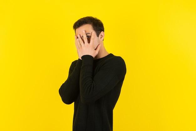 Portret van een jonge man in een zwart sweatshirt dat zijn gezicht bedekt op een gele muur