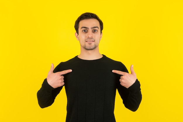 Portret van een jonge man in een zwarte sweater die staat en poseert voor de camera op de gele muur