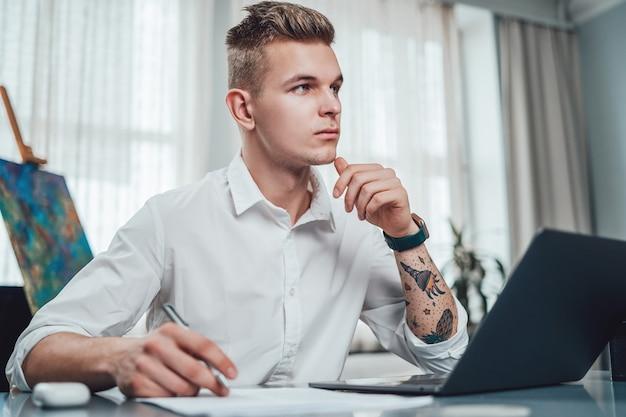 Portret van een jonge man in functie en zijn professionele bezigheid als fotograaf. mannelijke fotograaf in comfortabel kantoor overdag.