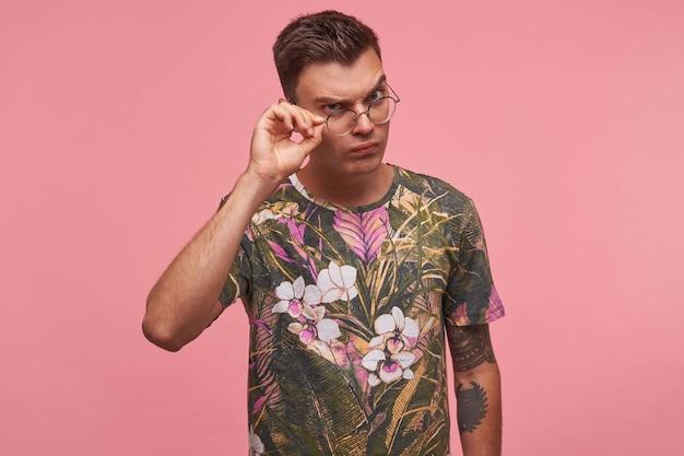 Portret van een jonge man in gebloemde t-shirt met verwarde gezichtsuitdrukking, kijkend door een bril met twijfels, geïsoleerd op roze achtergrond