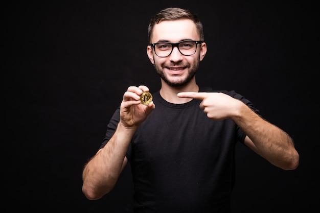 Portret van een jonge man in glazen slijtage in zwart shirt wees op bitcoin geïsoleerd op zwart