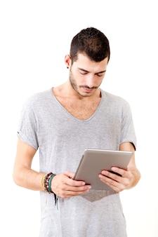 Portret van een jonge man in grijs shirt met behulp van tablet.