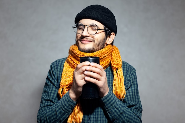 Portret van een jonge man in groen shirt met oranje sjaal en zwarte hoed