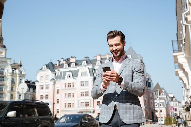 Portret van een jonge man in jas met behulp van mobiele telefoon